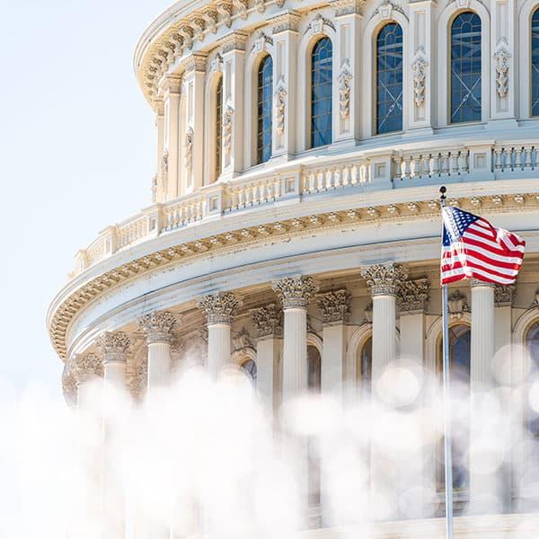 US Congress dome closeup with background of water fountain splashing, American flag waving in Washington DC, USA closeup on Capital capitol hill, columns, pillars,
